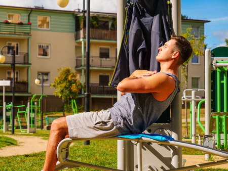 Young man working out in outdoor gym. Sporty guy doing abs exercises on machine. Staying fit and healthy.