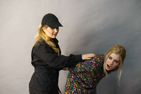 Shoplifting is a crime. Young fashionable woman being caught on stealing clothes by female security guard. Customer being thief. Reklamní fotografie