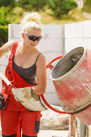 Strong woman worker working with shovel for sand and red concrete cement mixer machine on house construction site. Industrial work equipment concept. Zdjęcie Seryjne