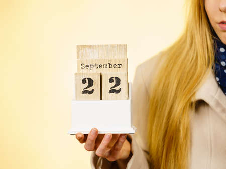 Woman holding calendar with first autumn day 22 september. Studio shot on yellow background.