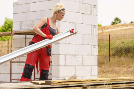 Woman carrying steel metal made gutter on her house construction site, building new home, fixing hydraulics