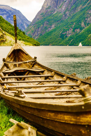 Old wooden viking boat on seashore in norwegian nature and ferryboat on fjord. Mountains and Sognefjord. Tourism and traveling concept Foto de archivo