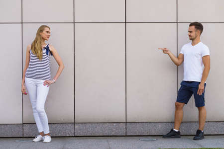 Young woman and man standing at wall. Guy point finger at girl.