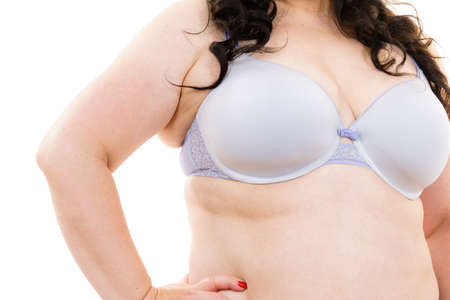 Plus size fat mature unrecognizable woman wearing comfortable bra, on white. Female breast in lingerie. Bosom, brafitting and underwear concept.