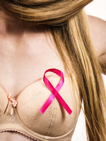 Woman wih pink ribbon on chest. Young female wearing bra lingerie showing symbol representing awareness, hope and moral support for breast cancer patients.