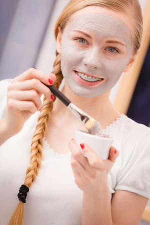Skincare. Young woman applying with brush grey clay mud mask to her face. Female taking care of skin condition. Spa beauty treatment.