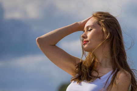 Young woman relaxing outdoor. Female enjoy sunlight against blue sky.