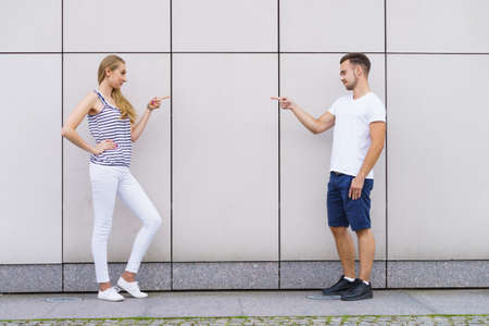 Young woman and man standing at wall. Couple pointing fingers at each other.