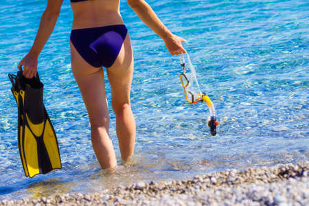 Woman back view with snorkel equipment flippers and snorkeling mask tube on beach sea shore. Summer vacation swimming fun concept. Foto de archivo
