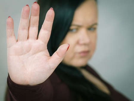 Woman saying stop. Plus size female showing denial hand sign gesture.