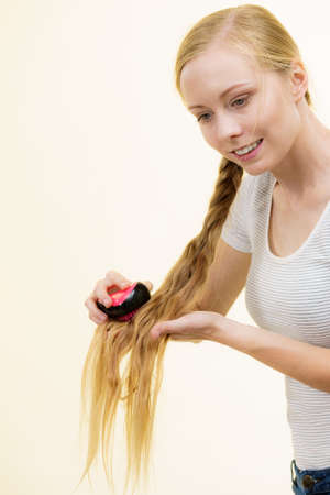 Blonde girl with long braid hair and brush. Girl taking care refreshing her hairstyle. Haircare concept. Stock Photo