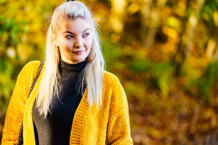 Woman wearing fashionable outfit yellow cardigan walking in autumnal park.