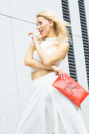 Attractive fashionable woman in trendy urban outfit white crop top trousers culottes posing outdoor. Female model holding red handbag.