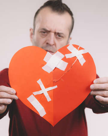 Bad relationships, breaking up, emotions concept. Funny adult man holding broken heart, on grey Stock Photo