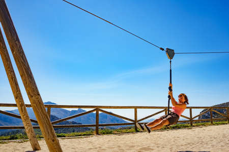 Adult freedom woman tourist having fun on zipline, descend on rope, cable aerial ropeslide. Mountains rest place in Spain Alicante region. Costa Blanca holiday. Stock Photo