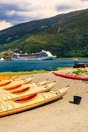 Kayaks on shore and cruise ship on fjord in norwegian tourist destination Flam village.