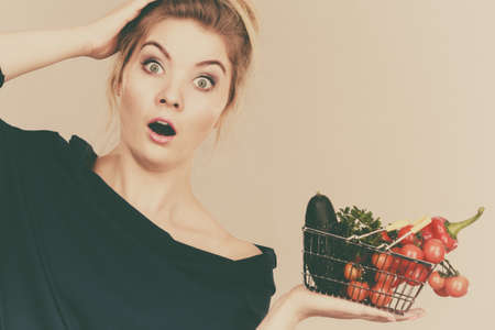 Adult woman do not like to eat raw food, questioning healthy lifestyle recommendations, origin vegetagles. Female holding small shopping basket with products, displeased shocked face expression