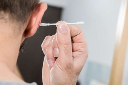 Man about to clean his ears using Q-tip cotton swab. Hygiene essentials concept. Removing wax from ear. Banque d'images
