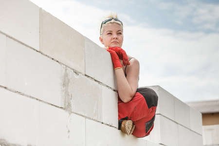 Woman wearing dungarees thinking about future of building her home. Female sitting on wall made of airbricks on construction site contemplating