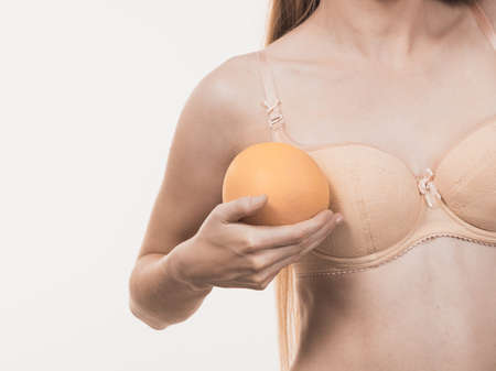 Slim woman small boobs wearing bra holding big grapefruits. Breast enlargement size correction concept. 스톡 콘텐츠