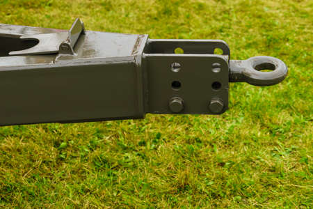 Close up on dark towbar in agricultural machine vehicle. Green grass in backround.