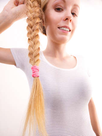 Blonde girl braid hair with pink ribbon bow. Haircare, hairstyling.
