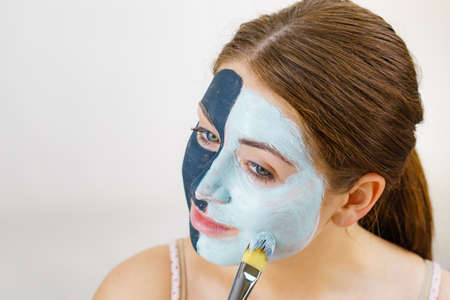Woman with clay carbo black mask on half face applying white mud to clean skin. Girl taking care of oily complexion. Beauty procedures. Skincare. Imagens