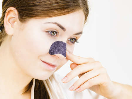 Woman appying clear-up strips on nose, using pore cleansing textile mask, on white. Girl taking care of skin complexion. Beauty treatment. Skincare.