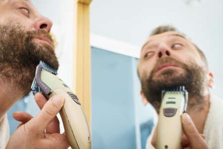 Bearded man looking at himself in mirror trimmng, shaving his beard using electric timmer razor.