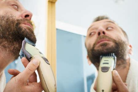 Bärtiger Mann, der sich im Spiegel betrachtet und seinen Bart mit einem elektrischen Timmer-Rasierer rasiert.