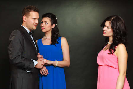 Love triangle concept. Man cheating on his wife, looking at other woman, choosing between two ladies.