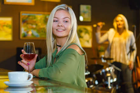 Girl with alcohol glass in club or bar at counter, female singer sing song in the background