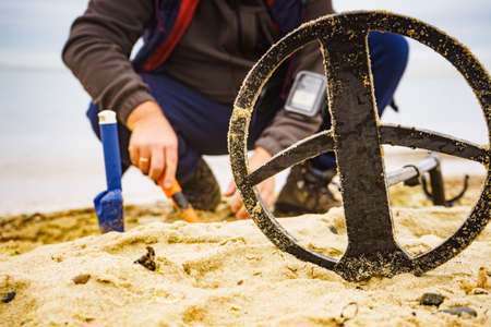 Man using electronic metal detector devic on sea sand beach. Detecting hobby. Banque d'images