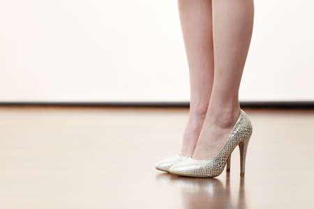 Unrecognizable woman wearing beautiful silver high heels standing straight. Legs shot only Foto de archivo
