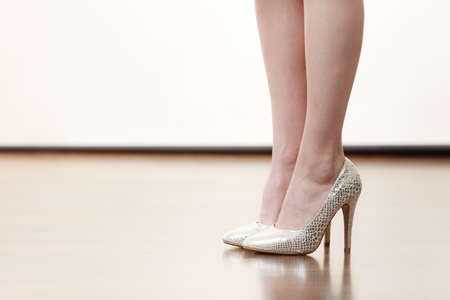 Unrecognizable woman wearing beautiful silver high heels standing straight. Legs shot only