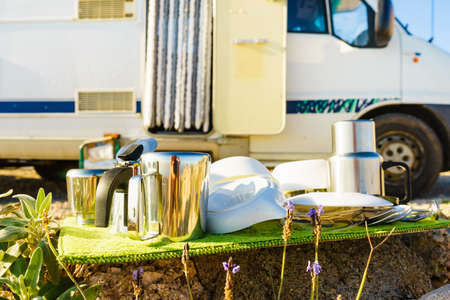 Many clean dishes outdoor on dish drying mat against camper vehicle. Washing up on fresh air. Camping on nature, dishwashing outside. Longing for an rv dishwasher. Stok Fotoğraf