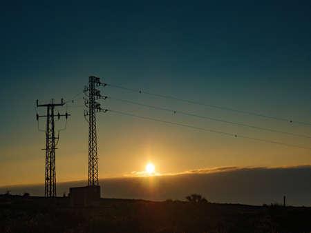 Electricity transmission pylons, power lines high voltage towers on spanish coastline. Sunset landscape.