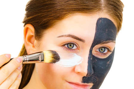 Woman with clay carbo black mask on half face applying white mud to clean skin. Girl taking care of oily complexion. Beauty procedures. Skincare. Foto de archivo