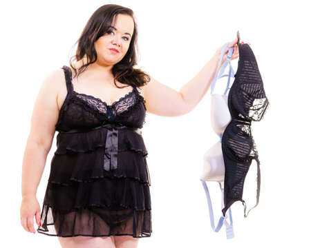 Plus size adult woman choosing perfect bra for her breasts. Female wearing sensual black chemise nightwear. Brafitting concept.