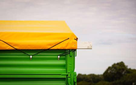 Yellow tarp tarpaulin fastened with rope to trailer