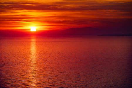Sunset over sea. Sun sinking below horizon.