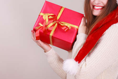 Gorgeous woman wearing santa claus hat holding red big gift box with ribbon. Xmas, happiness, winter and people concept. Banco de Imagens