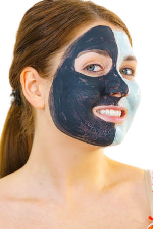 Woman with clay carbo black mask on half face and white mud on second half. Girl taking care of oily complexion. Beauty procedures. Skincare. Imagens