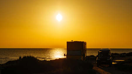 Camper recreational vehicle at sunrise on mediterranean coast in Spain. Camping on nature beach. Vacation and traveling in motor home.