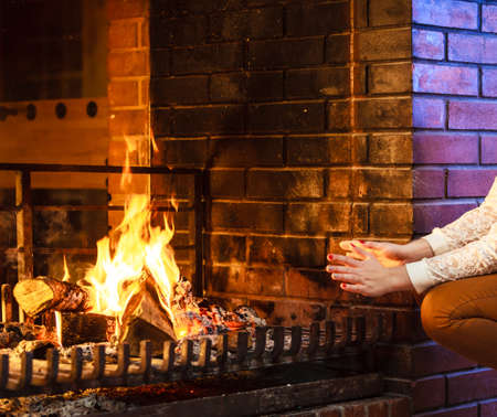Human warming hands up at fireplace. Person relaxing resting. Winter at home. 版權商用圖片