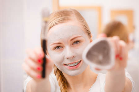 Skin care. Young woman holding in hands brush and clay mud mask to apply on skin face, in bathroom. Girl taking care of her oily compexion. Spa wellbeing. Banco de Imagens