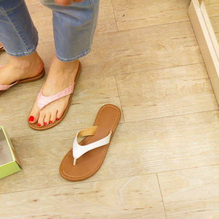 Unrecognizable woman trying on new flip flops in shop buying and choosing best footwear.