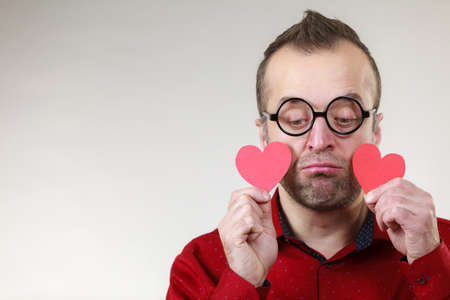 Adult serious man holding two red hearts. Romance love valentines day concept. Banque d'images