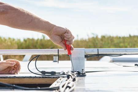 Male hands repair caravan motor home roof. 版權商用圖片