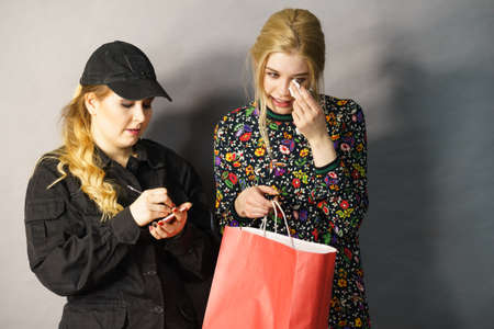 Shoplifting is a crime. Teenage girl being caught on stealing clothes by female security guard. Customer thief